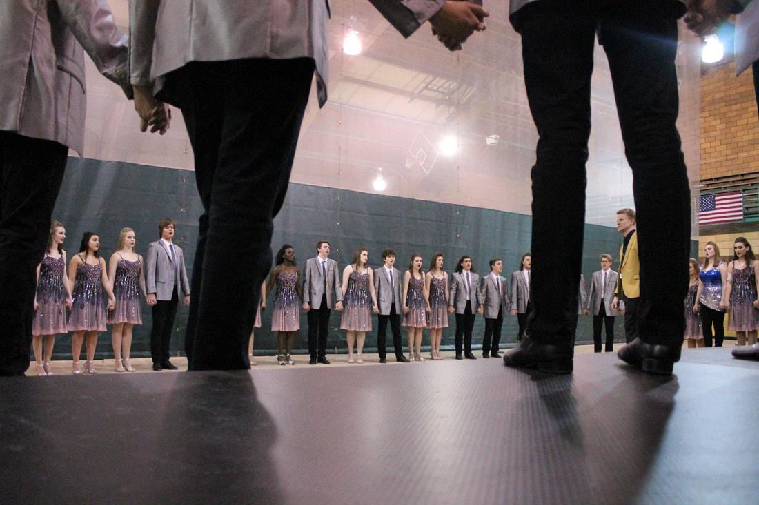 Good Time Company sing their ballad in a circle formation before going onstage at their first competition in Muscatine. (Lauren Ernst)