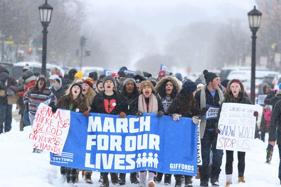 Members+of+Students+Against+School+Shootings+%28SASS%29%2C+hold+up+a+%22March+for+our+lives%22+banner+as+they+make+their+way+to+the+Pentacrest+on+March+24.+Nick+Pryor+%2718%2C+one+of+the+leaders+of+SASS%2C+was+impressed+by+how+many+people+came+out+in+the+snow.+%22It+was+a+nightmare+driving+downtown%2C+and+yet+nearly+a+thousand+people+came+out+to+support+the+movement%2C%E2%80%9D+Pryor+said.