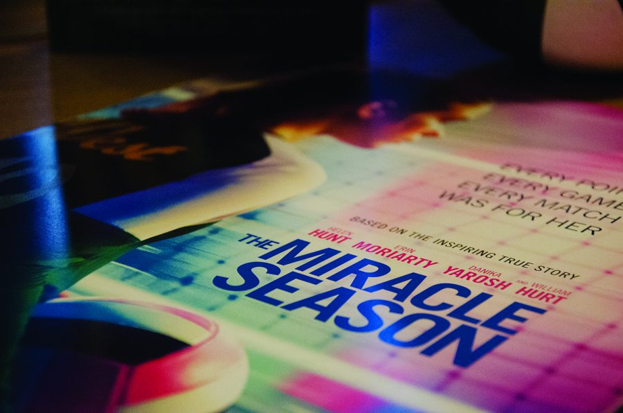 A poster for The Miracle Season sits on a table during a book signing.