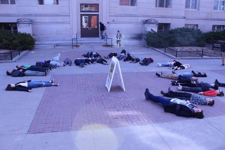 Demonstrators lie in a circle on T. Anne Cleary Walkway in front of Gilmore Hall.