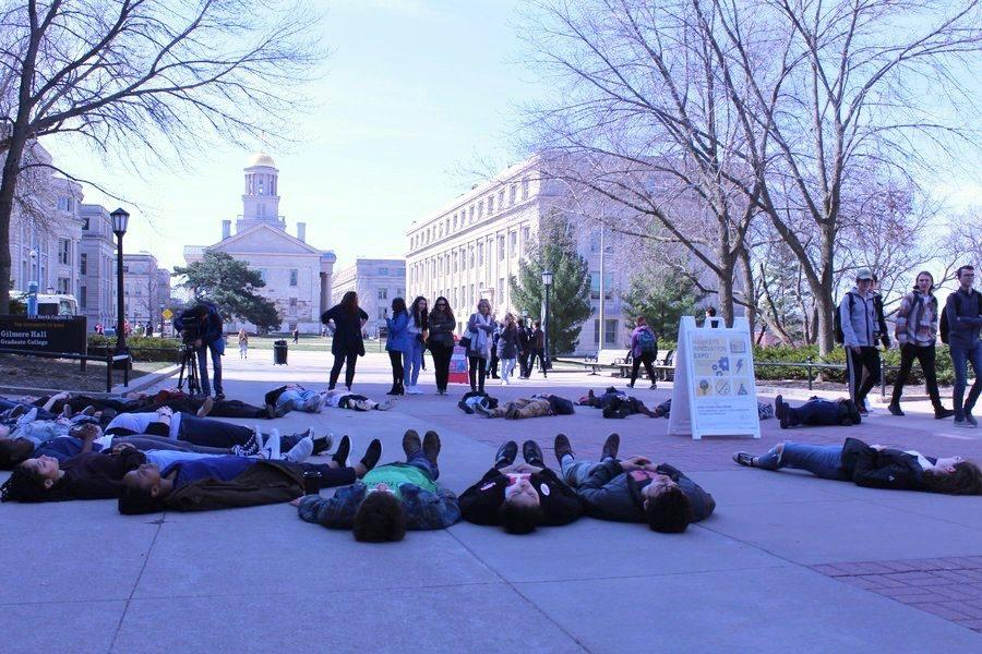 Students+lie+on+T.+Anne+Cleary+Walkway+in+protest+across+from+the+Old+Capitol++building+as+pedestrians+walk+by%2C+looking+on.