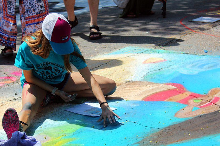 The artists smear pastel chalk to create the bold colors and cover the cement.