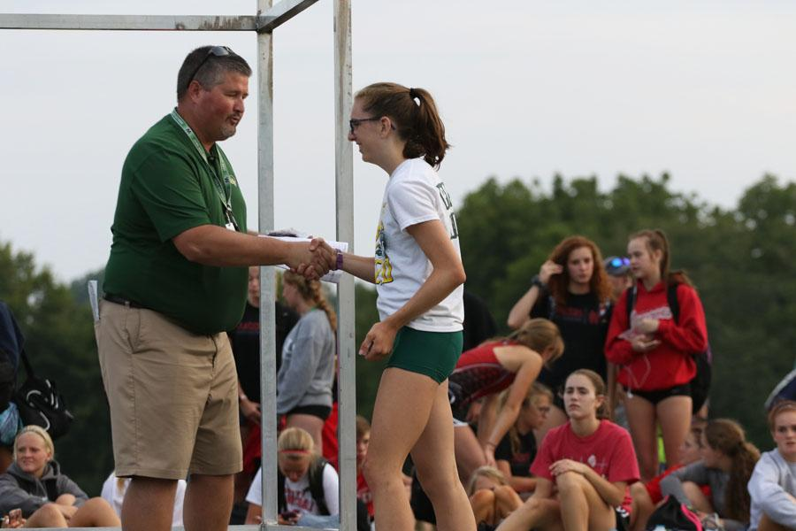 Erica+Buettner+%2721+shakes+hands+with+West+High+Athletic+Director%2C+Craig+Huegel+as+she+receives+an+award+for+9th+place.