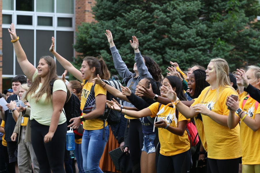 Students raise their hands in the air to grab a West High towel on Friday, Sept. 21.