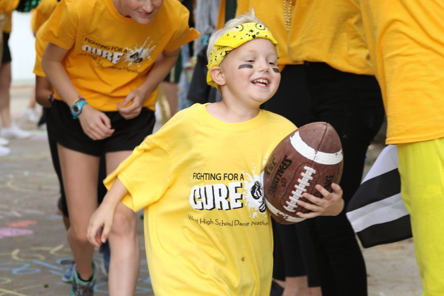 Kid captain Otto Phelps runs a football through a tunnel at the tailgate on Friday, Sept. 21.