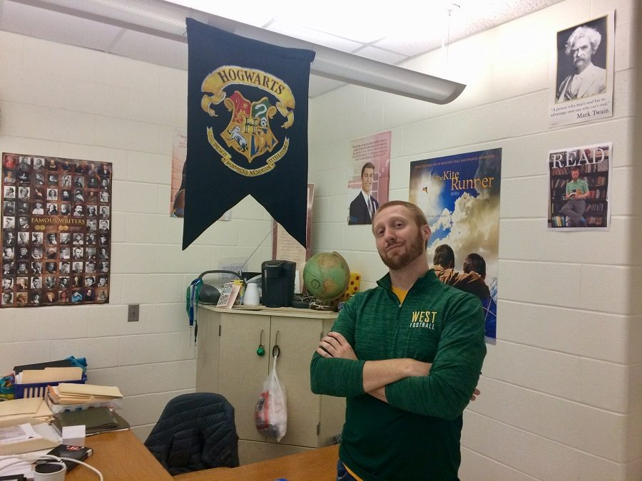 Mr. Cooper stands proudly in front of a Hogwarts banner in his room.