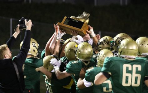 The team celebrates with the boot after their 54-13 win over City on Friday, Oct. 19, 2018.
