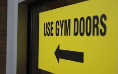 A sign telling visitors to use the gym doors hangs on a door leading to the commons on Tuesday, Oct. 2.