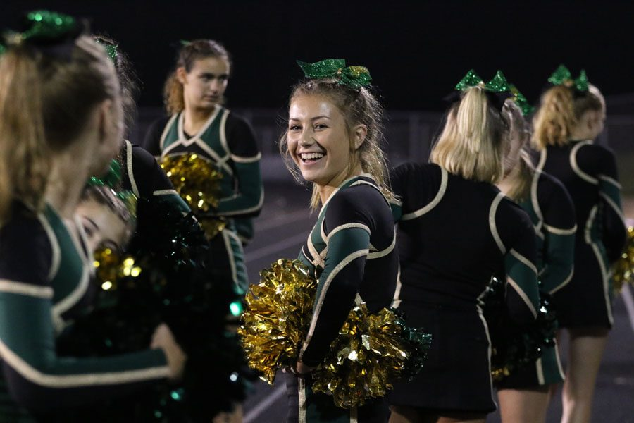 Austyn Goodale '20 stands on the sidelines as she cheers during the first home game against North Scott on Friday, Aug. 24.