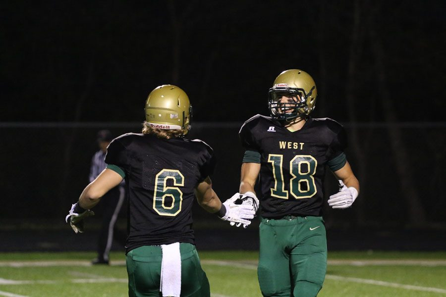 Mason Sorge 19 high-fives Cole Mabry 19 after Muscatine kicked a safety during the first half on Friday, Oct. 12.