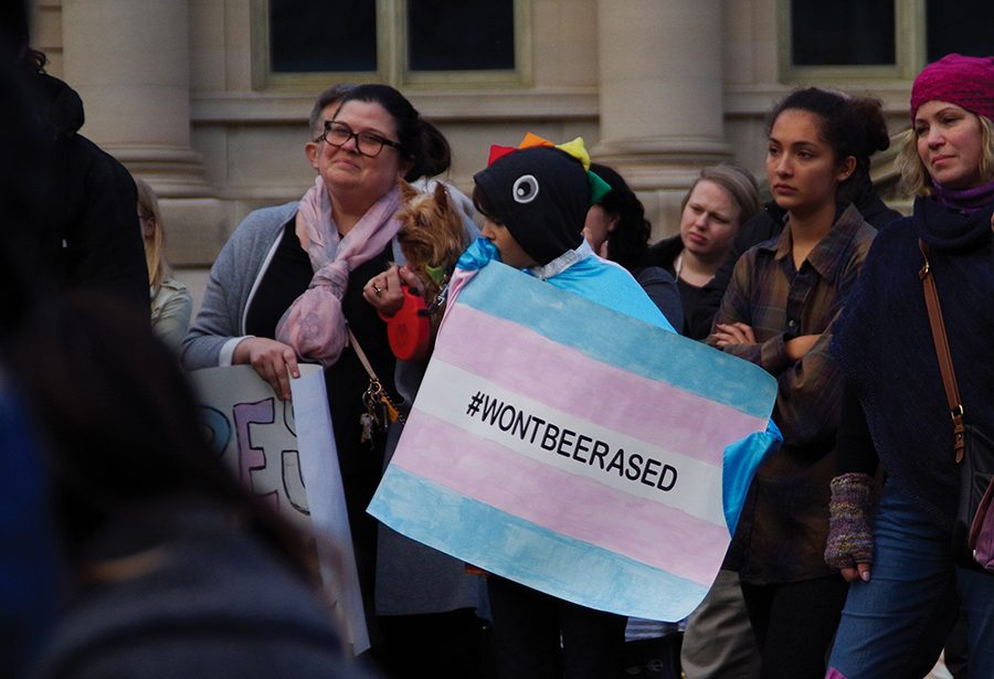 "Community members hold signs in support of transgender rights at a ""Support Trans Lives"" rally at the Pentacrest Oct. 25, 2018."