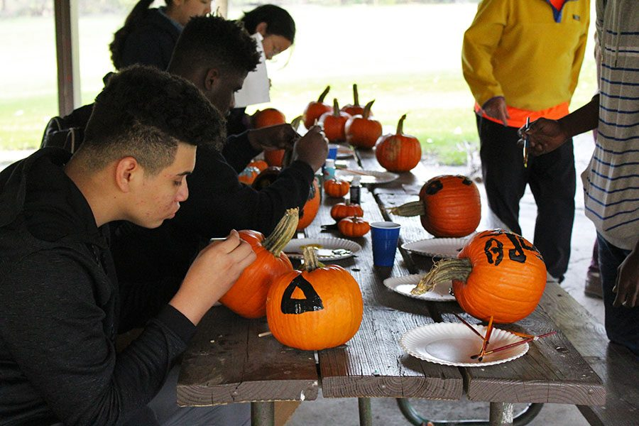 ELL students paint pumpkins into jack-o-lanterns during their event at Willow Creek Park on Wednesday, Oct. 24.