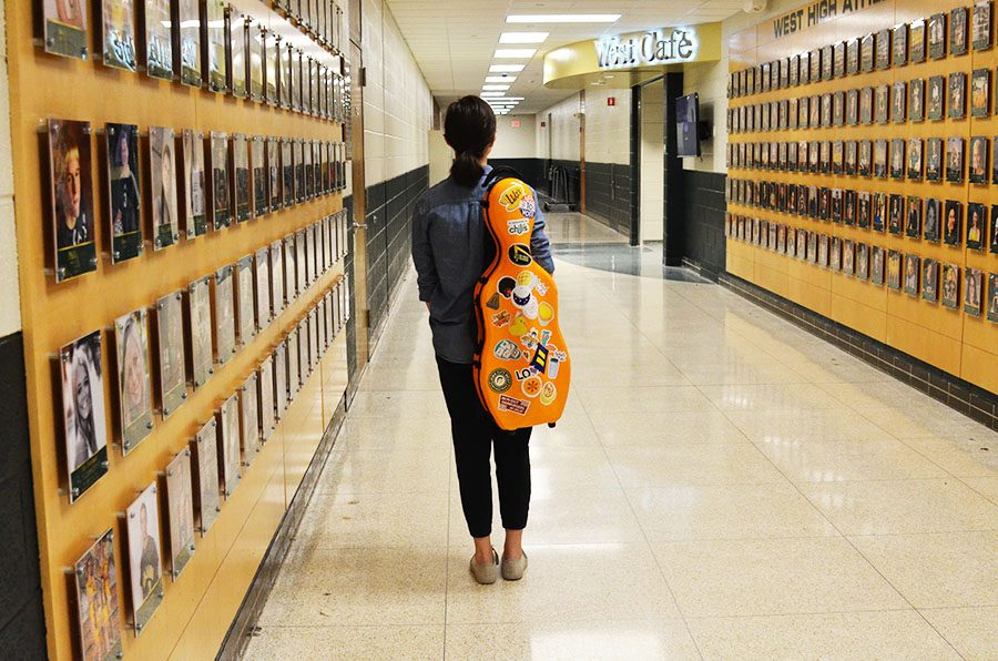 Perry Heredia '21 walks down the hallway with her viola on her back.