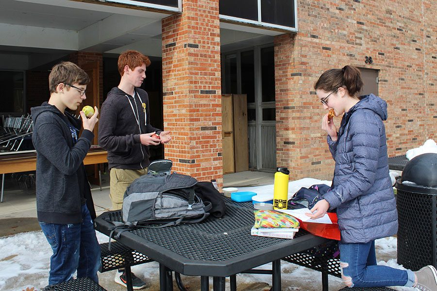 Liam Edberg '22, Tony Abdel Malek '22 and Claire Loussaert '22 eat lunch outside with a layer of snow on the ground on Friday, Nov. 30. The group has resorted to standing around a table while eating lunch because the benches are too cold.