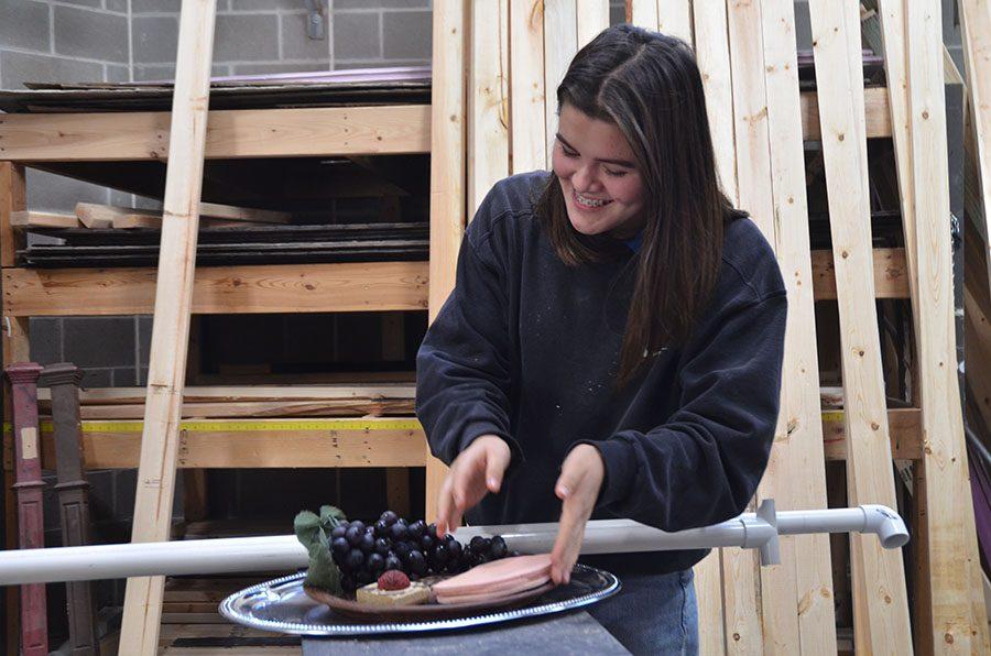 Frances Blount '21 arranges a plate of food as part of the set construction crew.