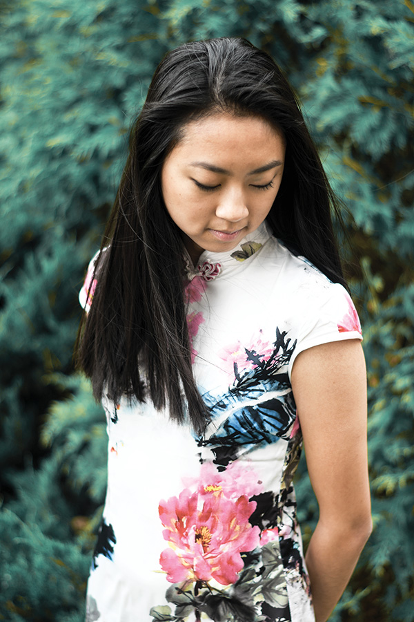 Rachel Ding '19 looks down while posing in a qipao. A qipao is a traditional Chinese dress typically worn during the Chinese New Year.
