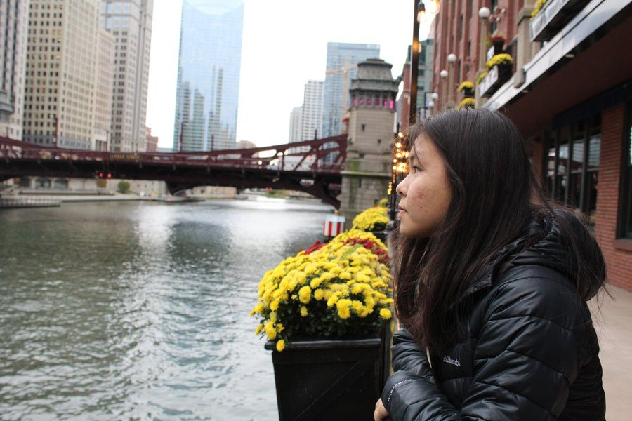 Designer Selina Hua 20 looks out over the Chicago River on the River Walk while sightseeing before heading to her design workshop on Thursday, Nov. 1.