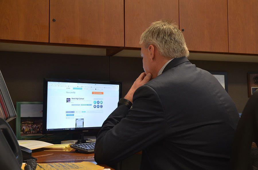Principal Gregg Shoultz looks through the weekly newsletter, published Sunday, November 4.