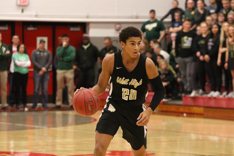 At+the+top+of+the+three-point+line%2C+Marcus+Morgan+%2721+dribbles+the+ball+as+he+waits+for+a+teammate+to+get+open+during+the+first+half+on+Friday%2C+Dec.+7.