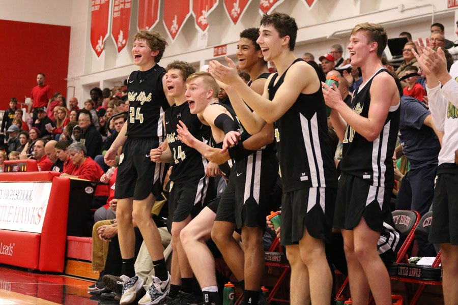 The Trojan's bench erupts in cheers after Charlie Moreland '20 scores a three-pointer during the second half on Friday, Dec. 7.
