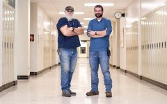 West janitors Ron Melsha and MJ Plank pose for a photo in the middle of the school hallways.