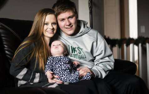 Sydney Johnston '19 and Noah Breitbach '19 hold their six-month-old daughter Stella Mae Breitbach while sitting in the living room in Sydney's house.