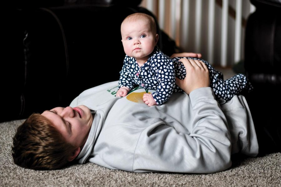 Noah Breitbach 19 holds Stella after playing with her on the floor. He says that, She just makes us laugh all the time.