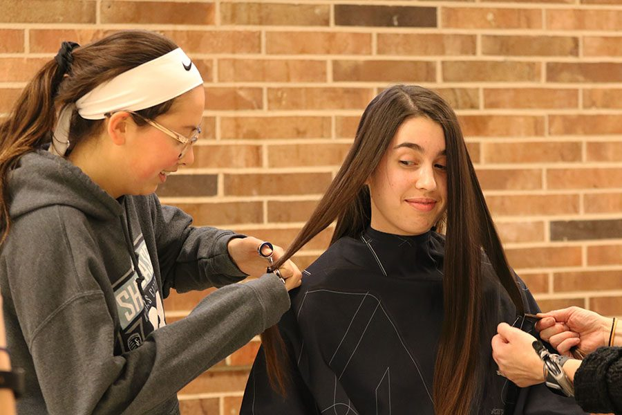 "Anna Moore '21 watches Julia Bernat '21 cut a strand of Moore's hair after school in the commons during the annual West High School Dance Marathon hair drive on Jan. 11. ""I had wanted to cut my hair for a few months,"" Moore said. ""[I] waited until the West High Dance Marathon hair drive because I knew people who had donated their hair in the past and I thought it sounded like a cool way to help out. It's a little thing to do for a great cause."""