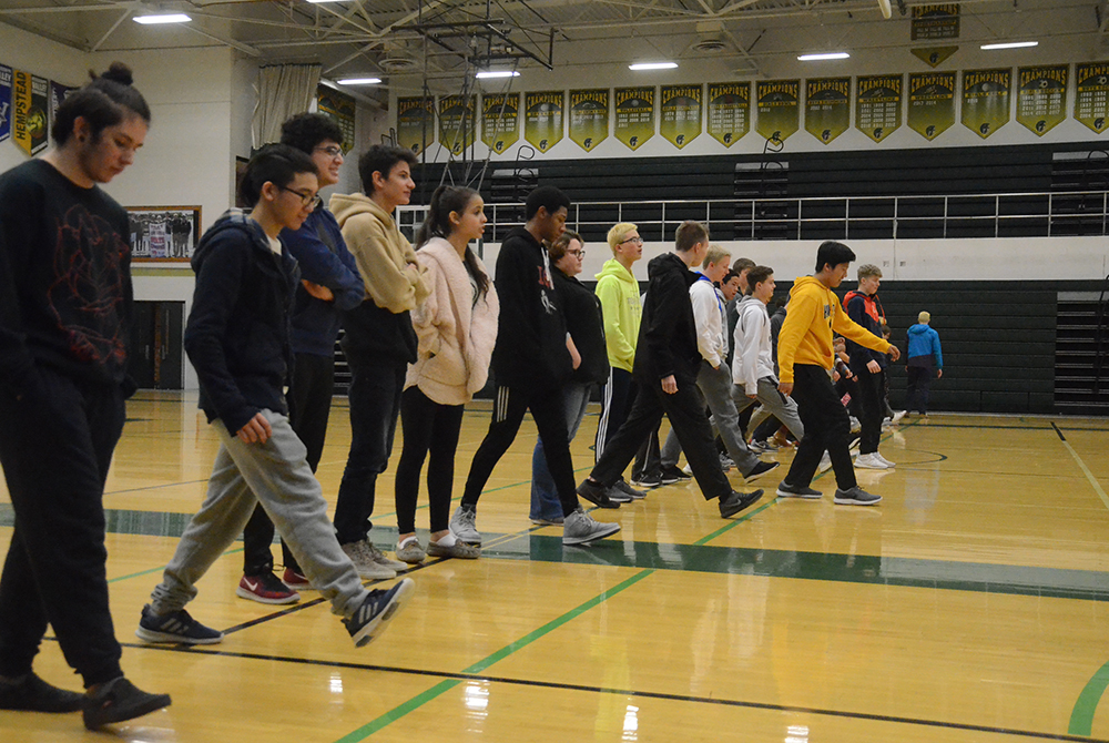 Students take a step forward during the Privilege Walk, a session aimed at visually portraying disparities in opportunities and advantages of varying backgrounds.