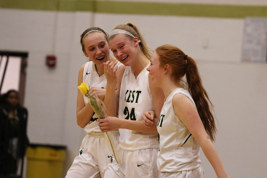 Emma Koch '19 sheds tears as she walks down the court with Audrey Koch '21 and Rylee Goodfellow '21 during the senior recognition after the game on Saturday, Feb. 16.