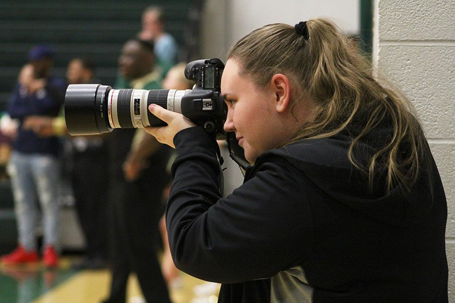 Online+Editor-in-Chief+and+Co-Sports+Editor+Kara+Wagenknecht+%2719+shoots+a+photo+while+covering+a+basketball+doubleheader+at+West+High+on+Saturday%2C+Jan.+5.