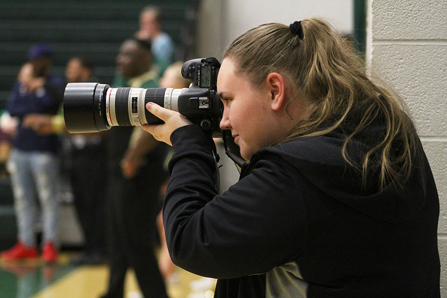 Online Editor-in-Chief and Co-Sports Editor Kara Wagenknecht '19 shoots a photo while covering a basketball doubleheader at West High on Saturday, Jan. 5.