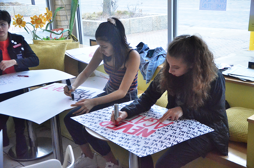 Olivia Barker '20 works on a sign at Yotopia for the gun reform march.