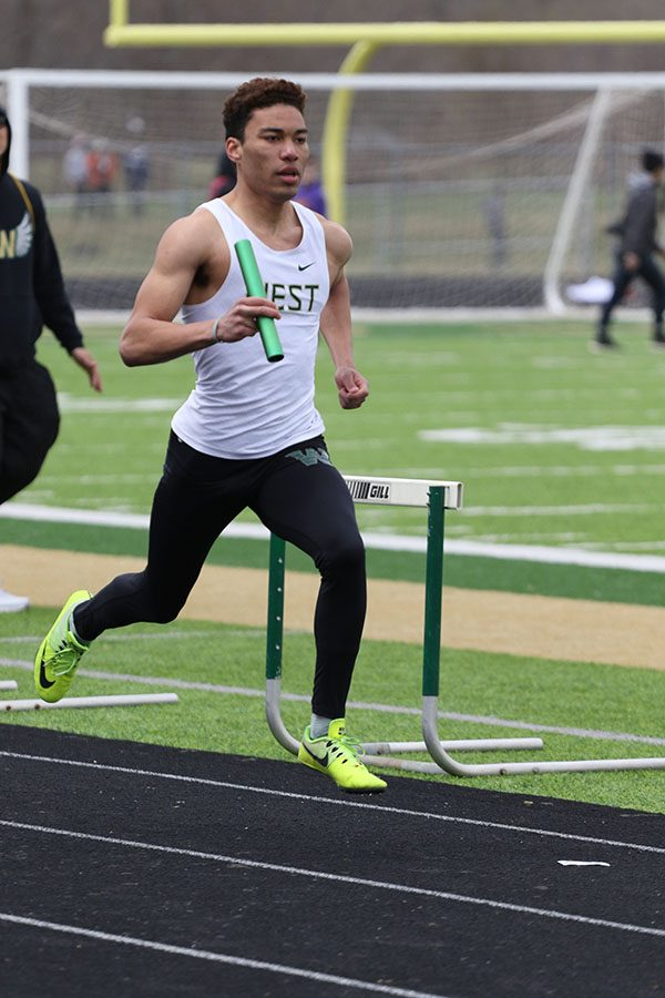 Gabe Caruthers 19 runs the 400 meter lap during the distance medley on Saturday, April 13. The relay team placed second in 3:41.68.