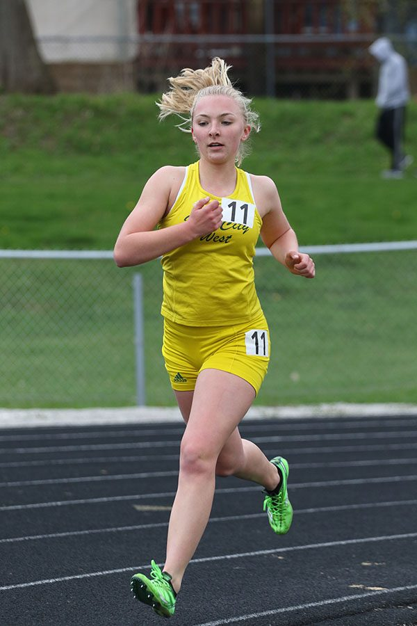 Katie Hoefer runs around the curve of the track during the 3000 meter run. Hoofer placed 11th in 11:42.99 on Thursday, April 18.