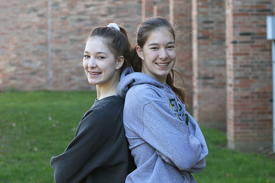 Twins Lizzy and Makayla Slade '21 stand side by side before school for a photo on Friday, April 19.