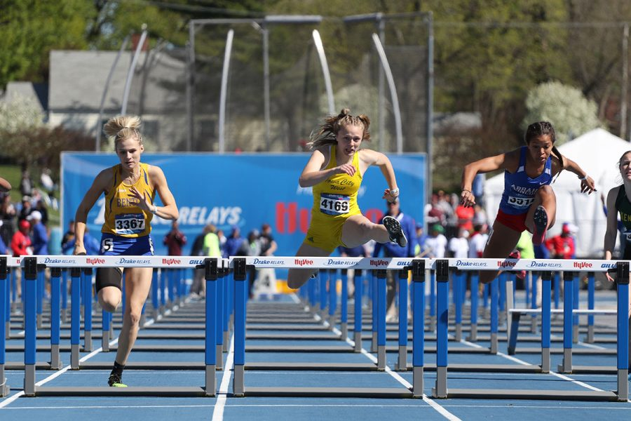 Peyton Steva 19 battles Abraham Lincolns Darby Thomas 19 as they both jump over the last hurdle during the 100 meter hurdle race on Friday, April 26. Steva fell by .03 seconds to Thomas to obtain second place with a time of 14.33.