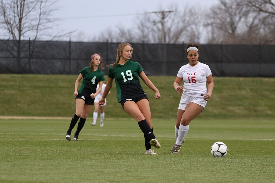 Rachel Olson 19 passes the ball to a fellow Trojan to gain momentum during the first half on Tuesday, April 9.