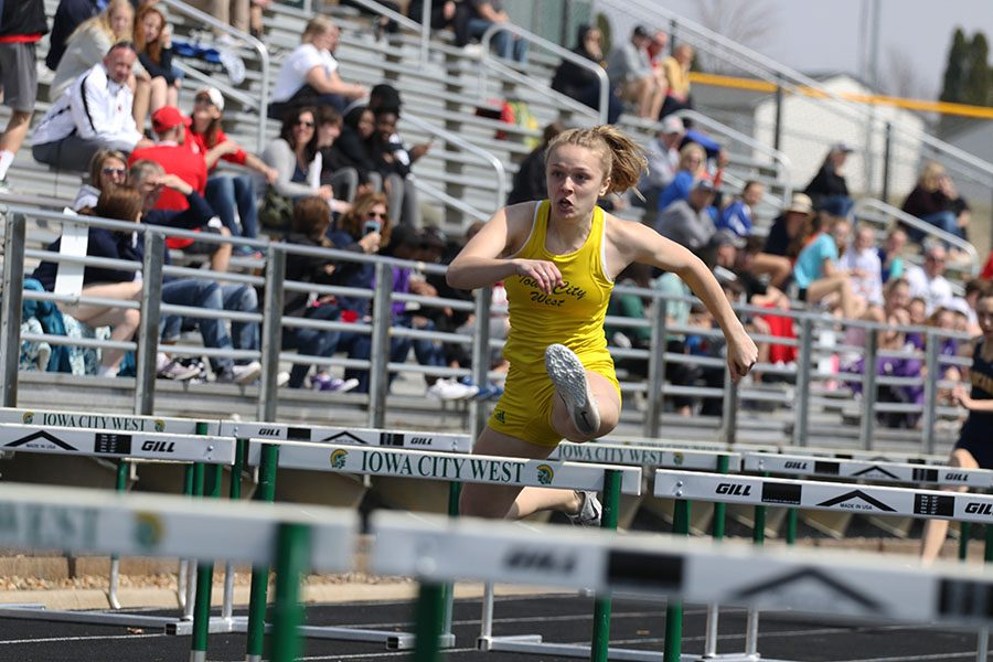 Peyton Steva 19 jumps over the seventh hurdle during the 4x100 shuttle hurdle relay race on Saturday, April 6. Steva also won in the 100 meter hurdles and became the new state leader in the event en route to qualifying for the Drake Relays with a time of 14.63.