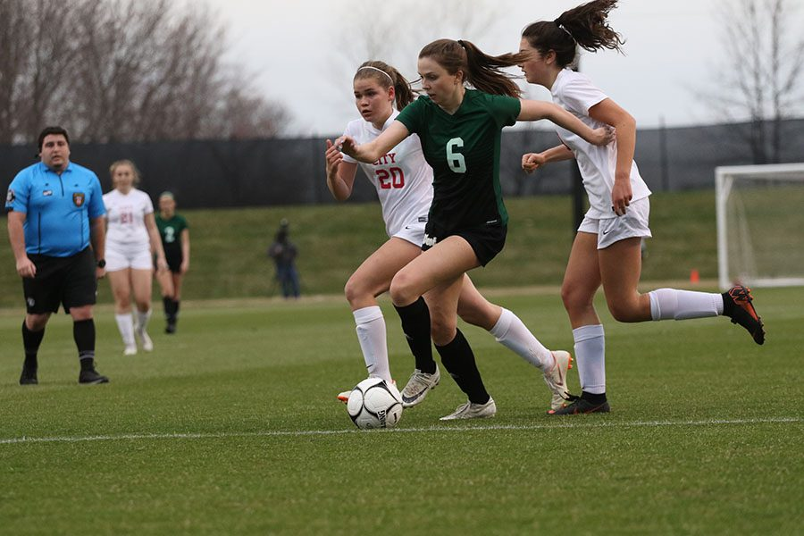 Hannah Cantrell 19 dribbles the ball towards the goal as City High defenders Muriel Brown 20 and Kate Wolfe 21 attempt to stop her during the second half on Tuesday, April 9.
