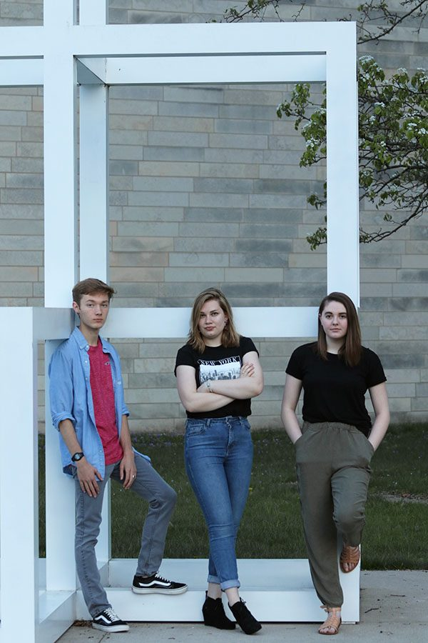 Seniors Will Conrad, Lucy Polyak and Sophie Stephens stand together against a sculpture downtown Iowa City on Sunday, May 5.