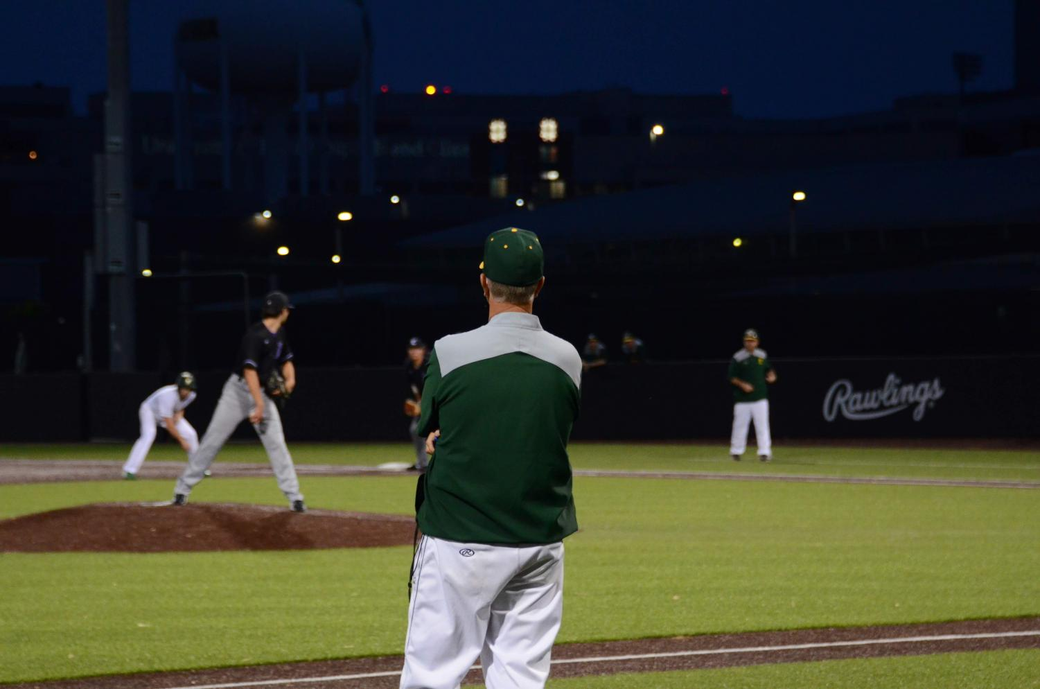 Head coach Charlie Stumpff observes the game from his position as third base coach during a game against Liberty on June 3.