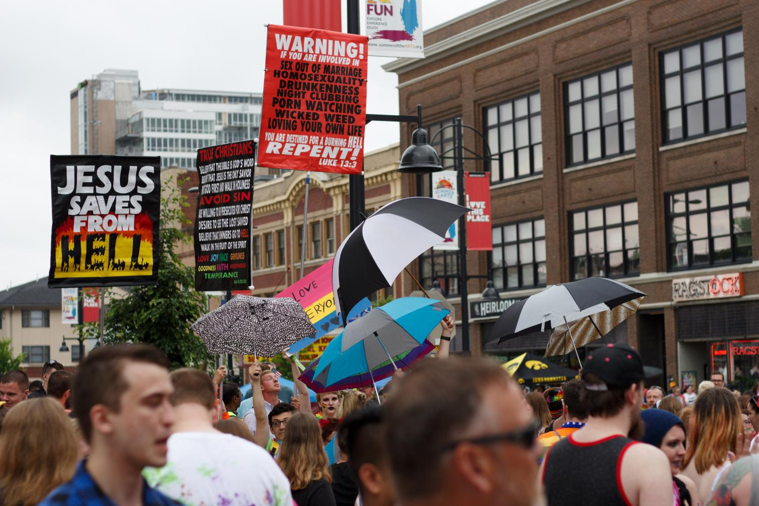 Protestors+of+the+event+held+signs+that+condemned+the+LGBTQIA%2B+community.+This+negative+presence+was+peacefully+met+by+attendants+of+the+festival+who+held+up+large+umbrellas+to+shield+the+signs+from+view.