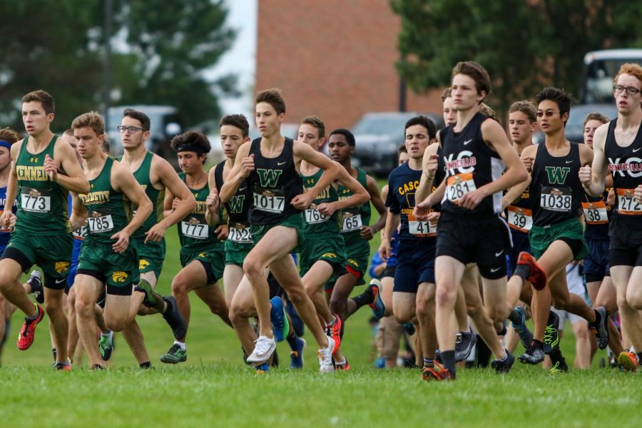 Alex McKane '22 and the Trojans sprint out of the starting line during the Prairie Invitational at Prairie High School on Aug. 31.