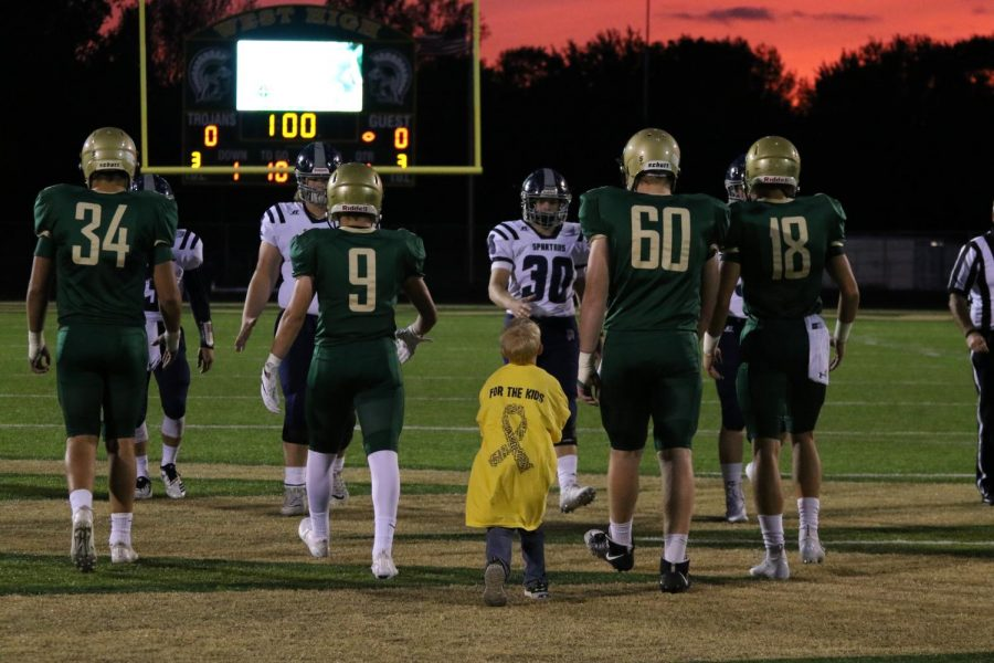 West High's 2018 gold out game kid captain, Otto, walks onto the field for the coin toss.
