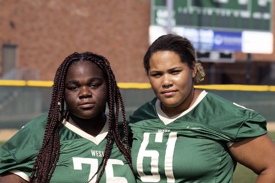 Teammates+Salima+Omari+%2720+and+Phoebe+Burt+%2721+stand+side+by+side+as+the+only+girls+on+the+2019+Varsity+football+team.+