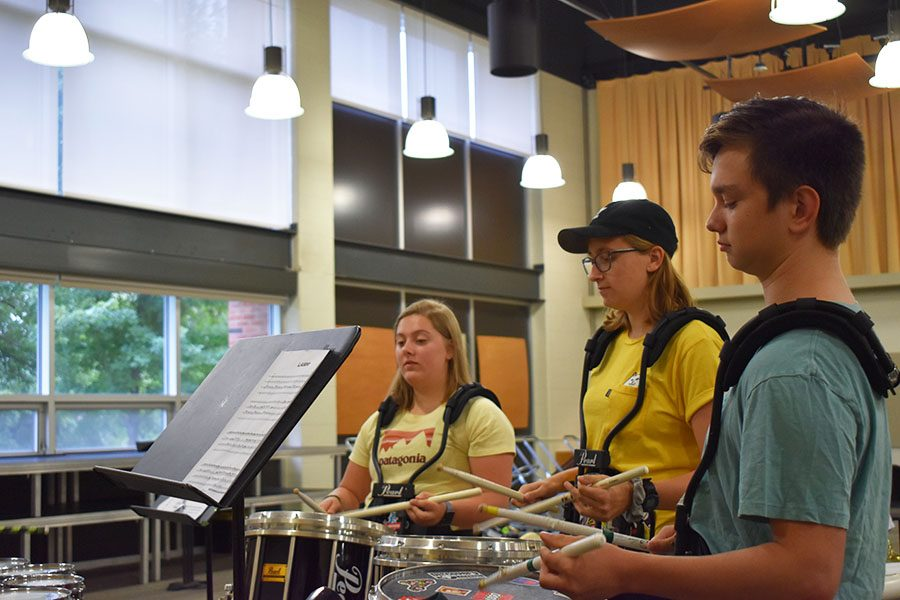 Noah Miller '21, Emily Hill '20 and Emma Christopher '22, members of the West High drumline play a cadence in the north band room.