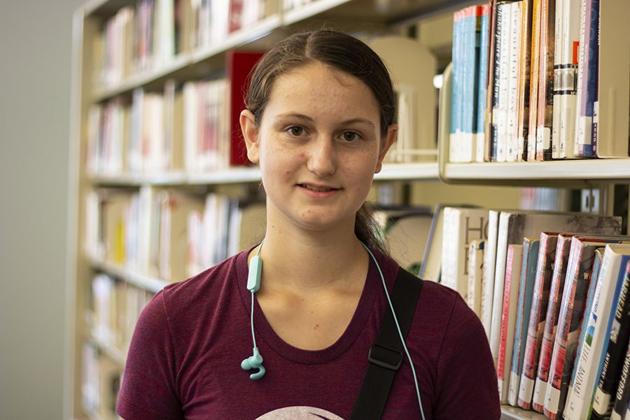 Renee Gould standing in front of a book shelf in the Iowa City West High library.