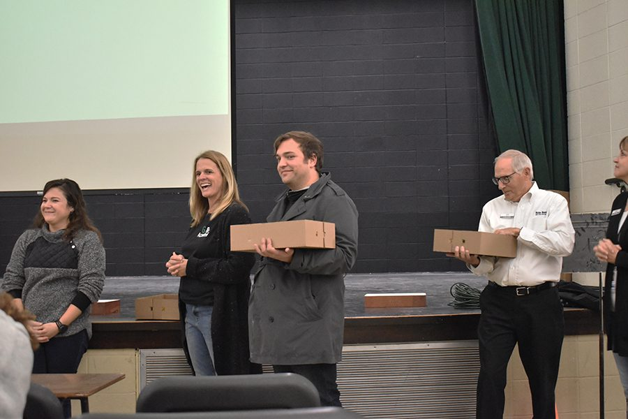 West High teachers Abbie Weipert, Kerri Barnhouse and Travis Henderson stand with Hills Bank representative Keith Jones before presenting the winning students with cupcakes.