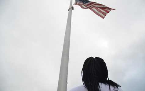 Reporter Mariam Keita '20 stands at the flagpole outside of West.